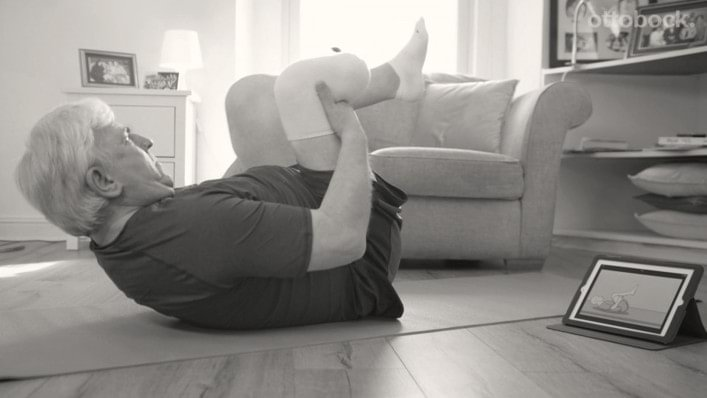 A man exercising while looking at a tablet