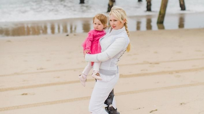 Kseniya standing on a beach holding her daughter