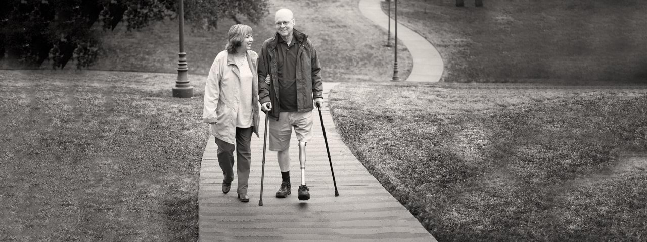 Alan wearing the Kenevo knee walking with his wife.