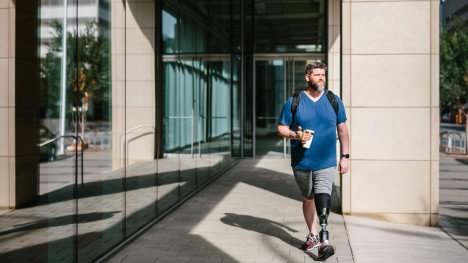 Rob walking outside with his Empower prosthesis near an office building.