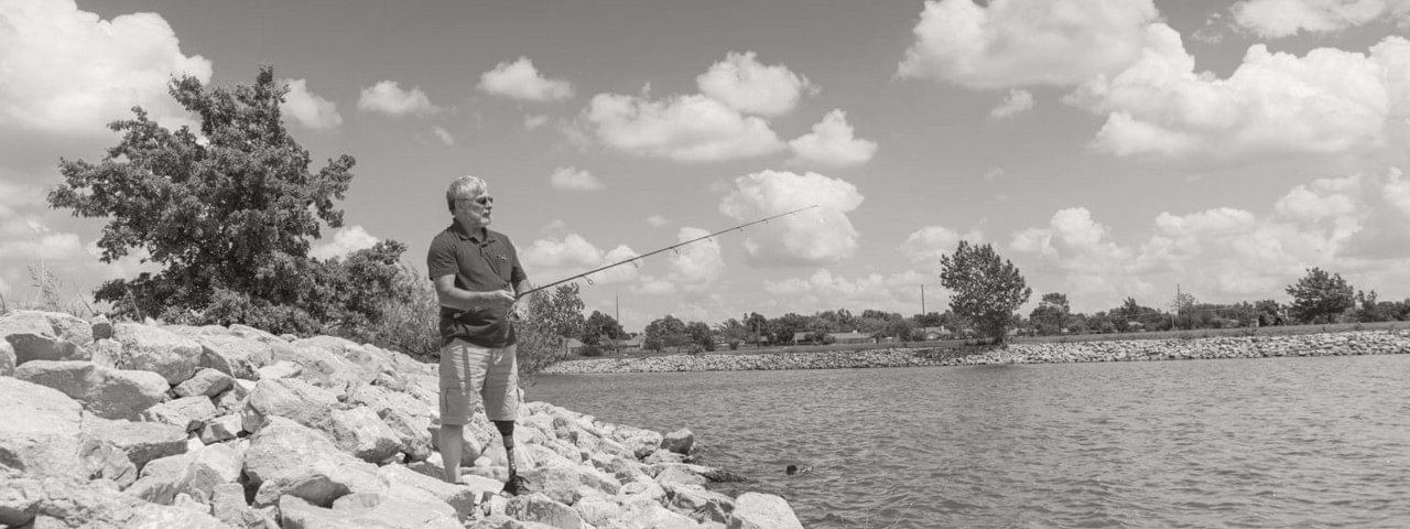 Steve fishing on a lakeshore while wearing his Harmony prosthesis