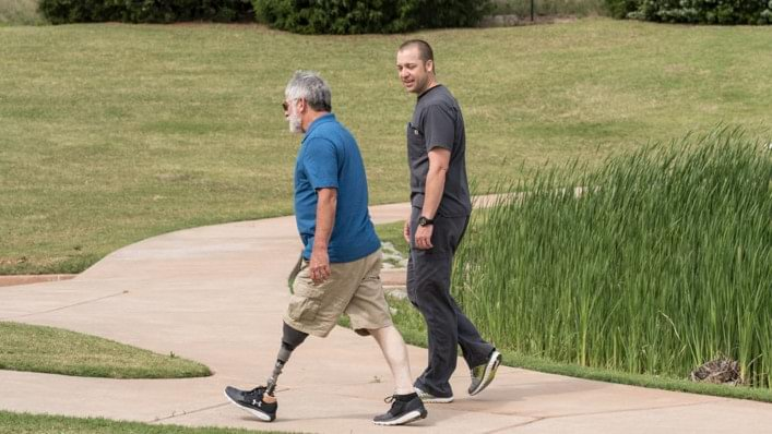 A Harmony user walking outdoors with his prosthetist
