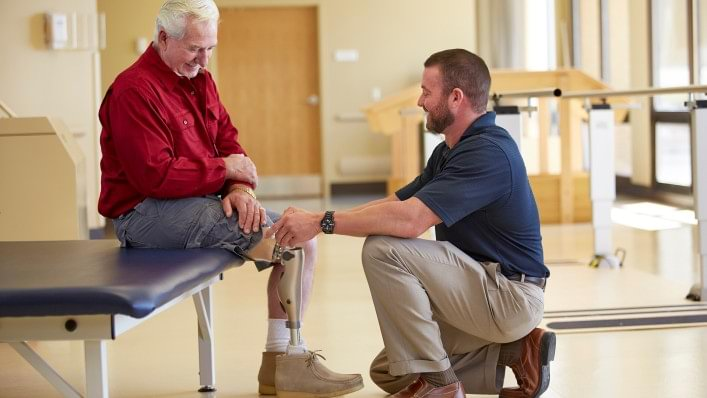Therapist working with seated man wearing a Kenevo prosthesis