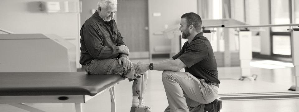 A therapist kneeling as he helps a patient wearing an Ottobock Kenevo prosthesis