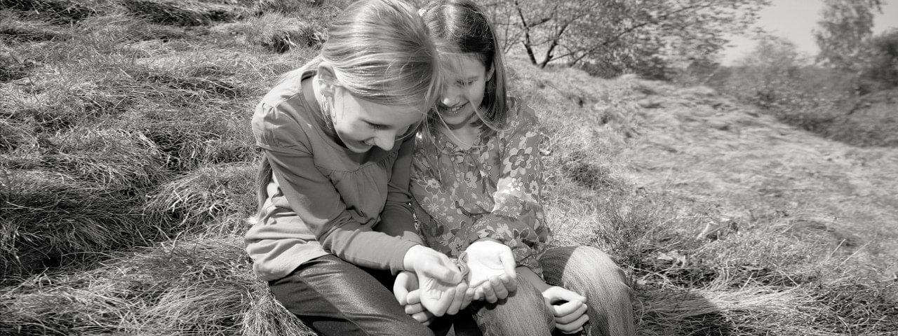 girls playing with salamander while one uses her electric hand 2000