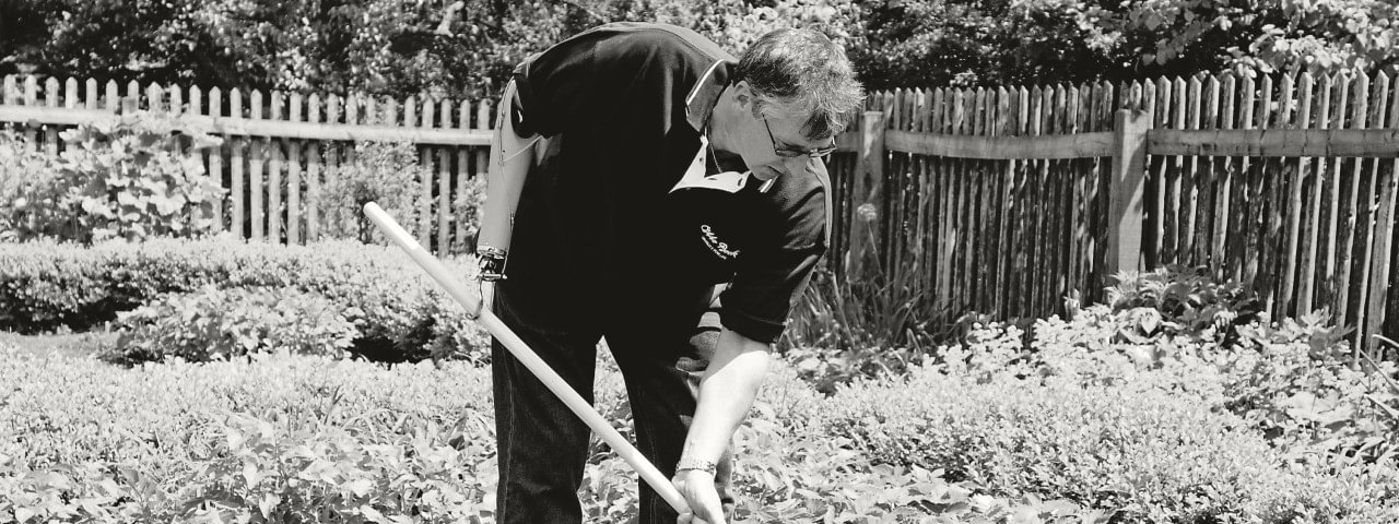 Man raking a garden while wearing body-powered hook